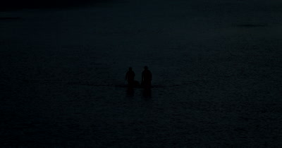Medium Shot of a Husband and wife heading back home after collecting Sea Cucumbers at sunset.