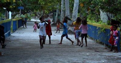 Village kids dancing with boat oars