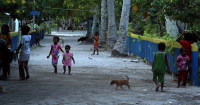 Village life on the street, where kids and dogs roam freely