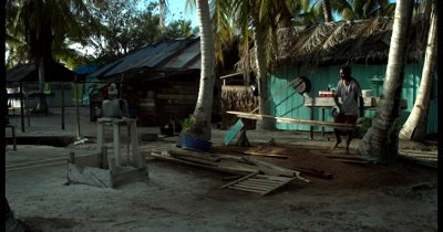 A villager working on wooden planks on the island, Palau Airborek