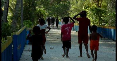 Village children walking down a road on the inhabited island, Palau Airborek