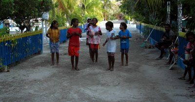 Village kids dancing to the rhythm of a guitar