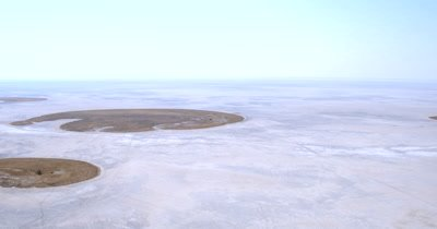 Aerial shot from the desolate Makgadikgadi saltpans  to the Savannah grass lands