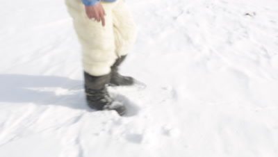 Musher putting chunks of snow in a cup to drink