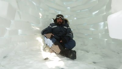 Man sitting inside of a small igloo