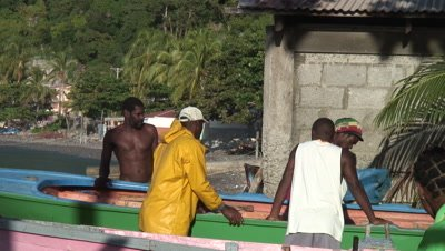 Caribbean fishermen around a boat,working and talking