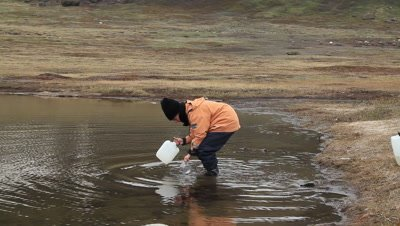 scientist collecting water samples from a small arctic freshwater lake