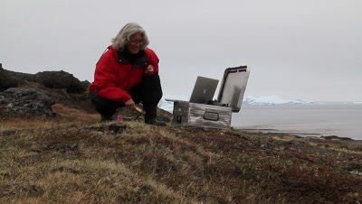 botanist working at the arctic tundra using a laptop