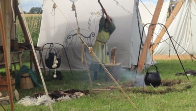 Young viking chopping firewood for the bunfire,kettle on the fire