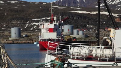 Ships in the harbor,village in the northern Greenland,oil storage in the background