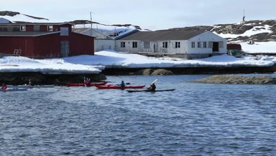 Kayaks,old inuit seal skin kayak and modern fiberglass kayak passing passing old storage buildings