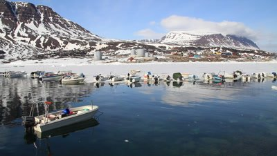 fishing boats pulled up on the ice,safe mooring ,inuit village,volcanic mountains and glacier in the background