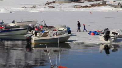 Inut fisherman and his son inspecting there fishing boat on the ice