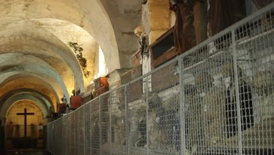 Corridor in the caputine catacomb in Sicily,mummies are protected behind a grid