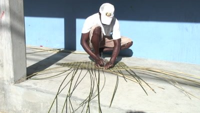 fisherman weaving a fishpot out of bamboo