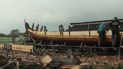 Boatbuilders working on the unfinished pricise copy of the Ladby vikingship.