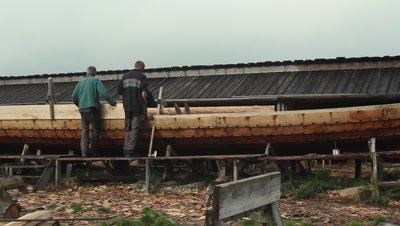 Boatbuilders working at the unfinished pricise copy of the Ladby vikingship.