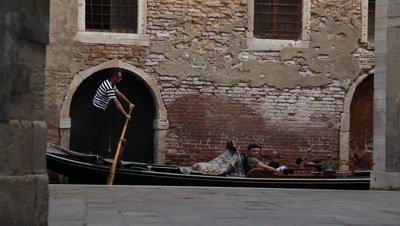 gonolas passing by at a narrow challel in Venice