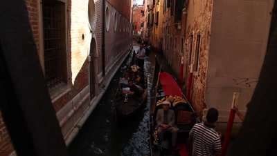 crowded gondola traffic in a narrow channel in the city of Venice