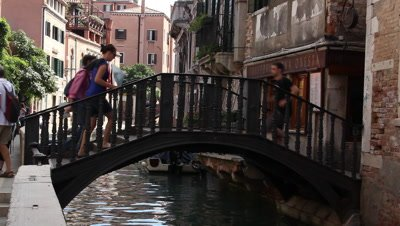 People passing an old traditional iron bridge in Venice