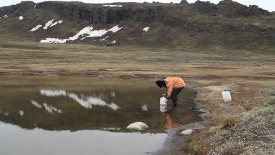 scientific assistant collecting water samples from an arctic freshwater lake