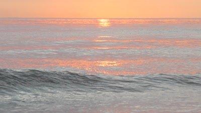 reddish gold ocean with long sun reflection