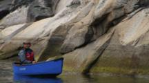Canoeing Past Rocky Shoreline On Ocean, Near Qikitarjuaq, Baffin Island