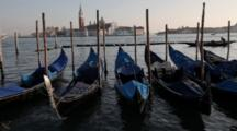Venice, Italy. Moored Gondolas In Foreground, Looking To San Giorgio Maggiore As Two Lido Car Ferries Cross.