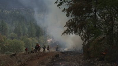 Firefighters stand in clearing at edge of wildfire in blowing smoke