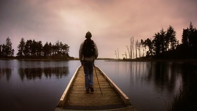 Young man hiking on dock on lake