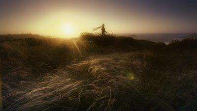 Woman with scarf walking in the wind,Cape Blanco,OR