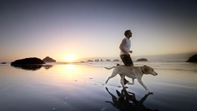 Boy running with his dog,Bandon,Oregon