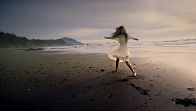 Young woman dancing on beach at sunset Port Orford,OR
