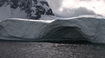 Antarctic Scenic Shoreline With Mountains Tracking Past Large Iceberg With Interesting Shape