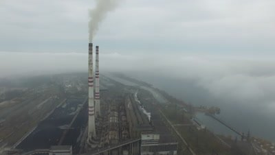 Aerial view of coal power station with smoke goes from tubes. Fog or clouds cover the land. View from the birdВ's-eye view.