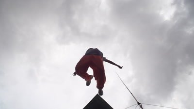 Slow motion shot of a young male parkour free runner jumping from roof