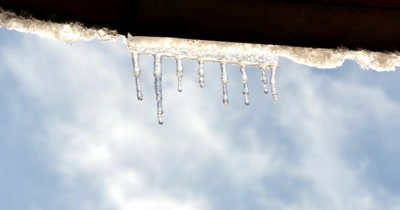 Water dripping from icicles on a roof after a snow