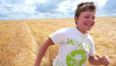 Young boy running through wheat field in sunny day