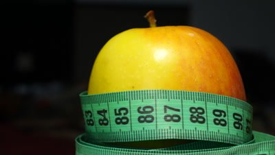 4k Green, juicy and fresh apple with measuring tape on black background, rotation, loopable
