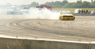 Participant in a drifting competition and burning tires on drag race track
