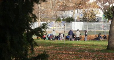 A large group of syrian refugees resting in a park