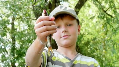 A boy holding a small river fish in hand slow motion