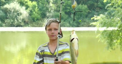 A little boy caught a fish on a fishing rod