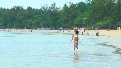 Healthy fit woman in bikini walking with surfboard on ocean beach. Extreme summer water sports.