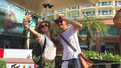 Portrait of beautiful traveling couple, make selfie of their Asia trip, happy laughing couple, couple in sunglasses, emotional man and tongue girl, crazy selfie