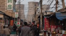 Local Chinese People Walk Through A Market Area In The Shadow Of The Giant Chimneys Of A Massive Coalburning Power Station. Sihui, Beijing, China