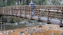 Water Polluted By Iron Enters Stream, Man Walks Across Bridge