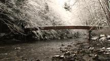 A Snow  Scene. A Bridge Crossing A Small Stream.