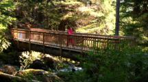 A Hiker Walks Across A Bridge.