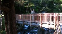 A Hiker Walks Across A Bridge.